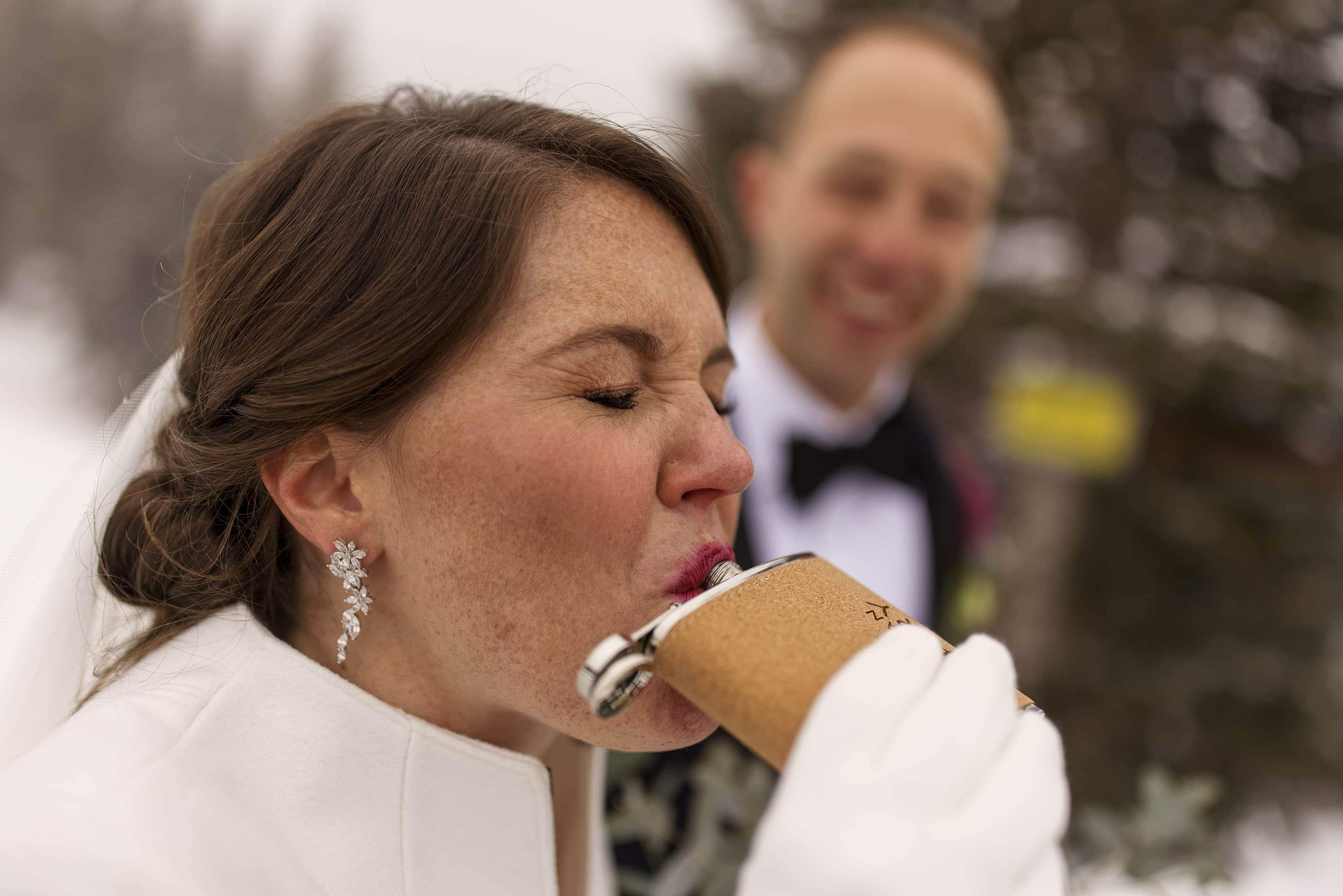 The bride takes a pull off a flask