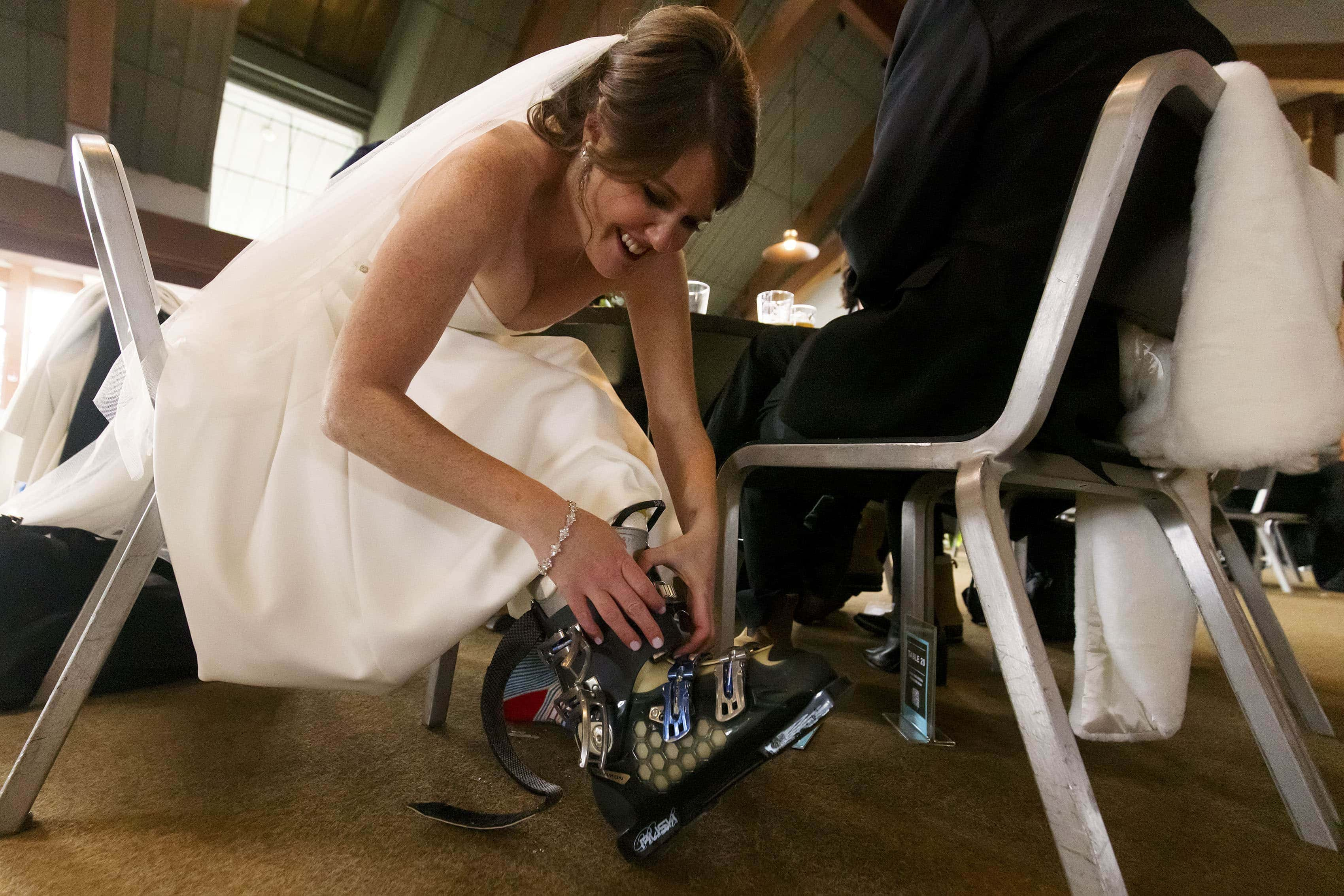 The bride puts on her ski boots in the lodge atop Aspen mountain