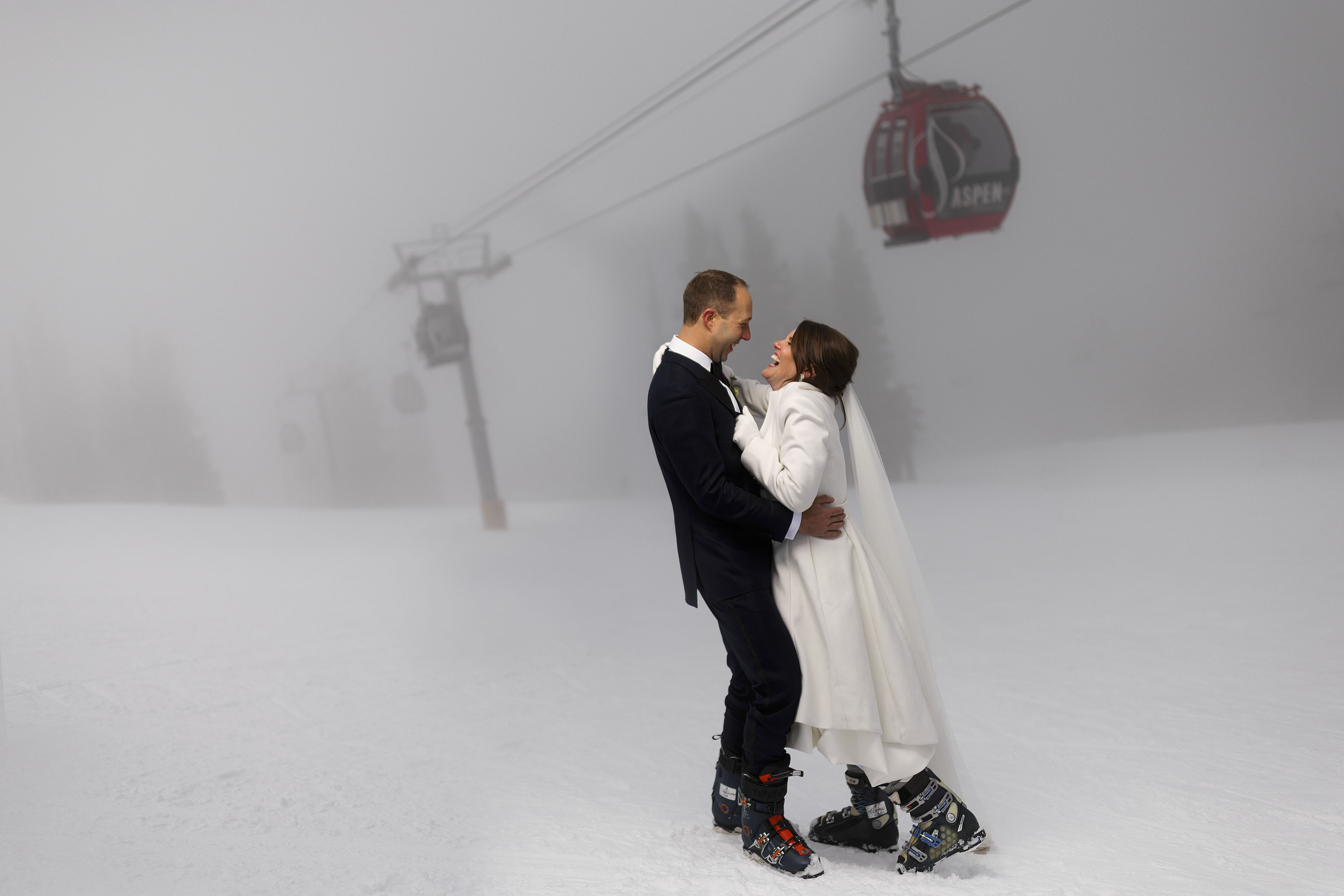 The bride and groom share a laugh while posing for a portrait as the fog rolls in on Aspen mountain following their micro wedding ceremony